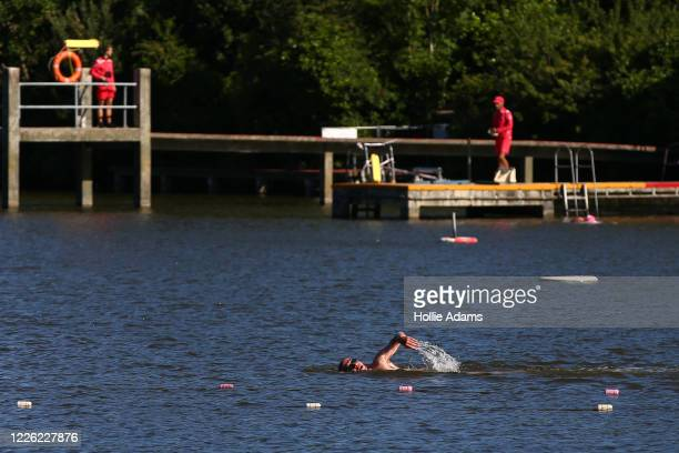 People swim at Hampstead Heath men's bathing pond which reopens to the public today on July 11, 2020 in London, England. The UK Government announced...