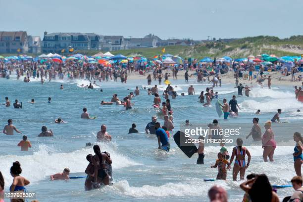 People swim at Hampton Beach in Hampton New Hampshire on August 5 as COVID19 cases in New England are on the rise Hampton Beach is close to the...