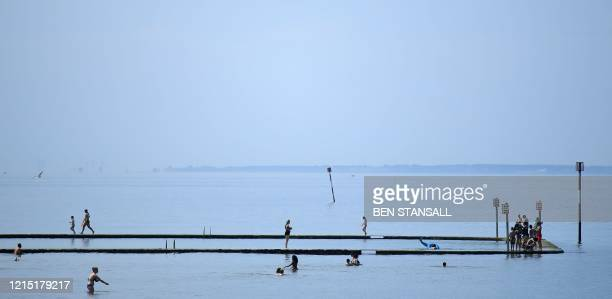 People swim in a bathing pool in the sea in Margate south east England on May 26 after some lockdown restrictions put in place to slow the spread of...