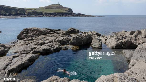 People swim in a natural sea pool exposed at low tide at Cape Cornwall on April 17, 2021 in Cornwall, England. With international travel restrictions...