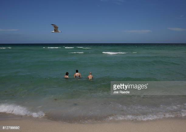 People swim in the ocean off of Haulover Beach where a rare shark attack occured on Sunday afternoon on July 11 2017 in Sunny Isles Florida MiamiDade...