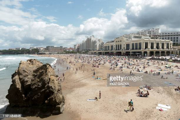 People swim in the sea and walk on the beach next to the municipal casino on the La Grande Plage beach in Biarritz on August 13 2019 The French...