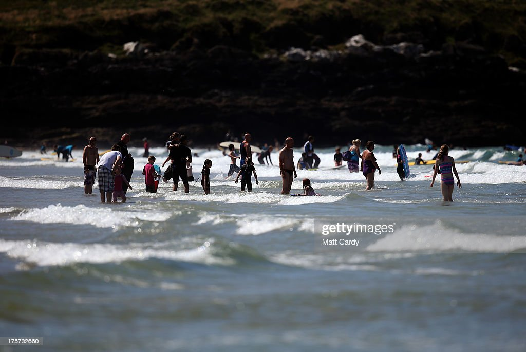People swim in the sea as Boardmasters pro-surfing competition takes place on Fistral Beach on August 7, 2013 in Newquay, England. Since 1981, the Boardmasters surfing competition - which is part of a larger five-day surf, skate and music festival - has been an integral part of the British surf scene and has grown from humble beginnings, to one of the biggest events on the British surfing calendar. It now attracts professional surfers from across the globe to compete on the Cornish beach that is seen by many as the birthplace of modern British surfing.