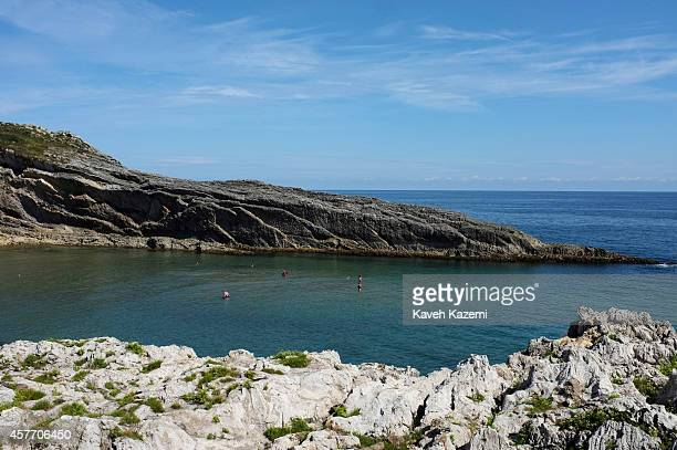 People swim in the sea on August 24 2014 in Llanes Spain Llanes is a municipality of the province of Asturias in northern Spain Stretching for about...