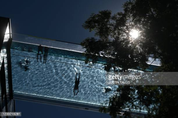 People swim in the Sky Pool - a transparent acrylic swimming pool bridge that is fixed between two apartment blocks - Embassy Gardens next to the new...