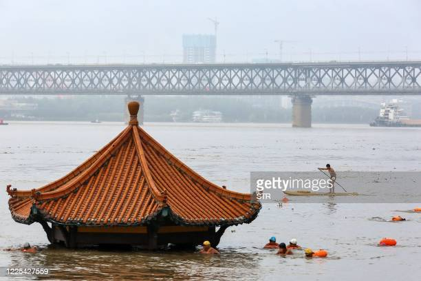 People swim in the swollen Yangtze River as the roof of an inundated pavilion is seen above floodwaters in Wuhan in China's central Hubei province on...