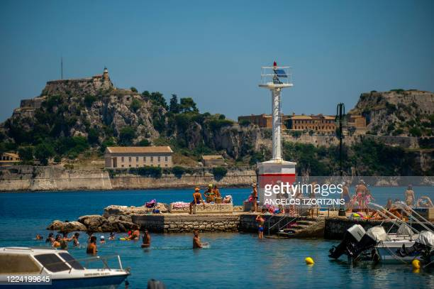 People swim near a pier in the island of Corfu on July 1, 2020 as the island welcomes its first tourists after months of closure due to the spread of...