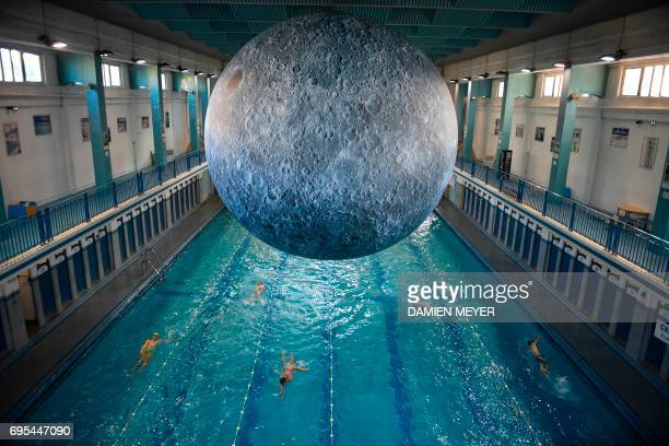 TOPSHOT People swim under an artwork 'Museum of the Moon' by British artist Luke Jerram at the SaintGeorges swimming pool in Rennes western France on...