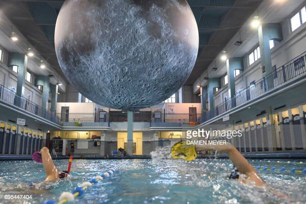 People swim under an artwork 'Museum of the Moon' by British artist Luke Jerram at the SaintGeorges swimming pool in Rennes western France on June 12...
