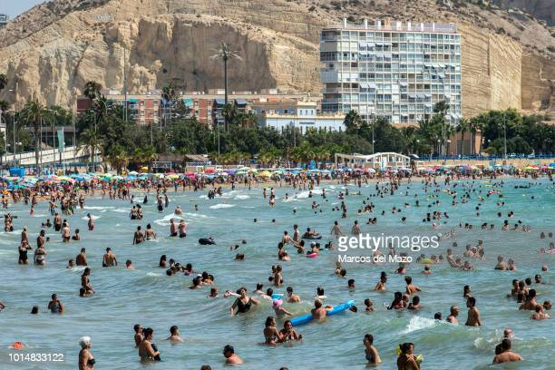People swimming at El Postiguet beach during a summer with high temperatures