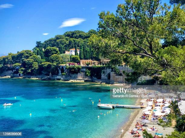 people swimming in pool by sea against sky - saint jean cap ferrat stock pictures, royalty-free photos & images