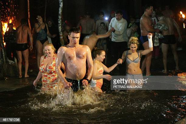 People take a bath in an ice hole of a frozen lake to celebrate Russian Orthodox Epiphany in Vilnius on January 19 2015 Among Orthodox Christians the...