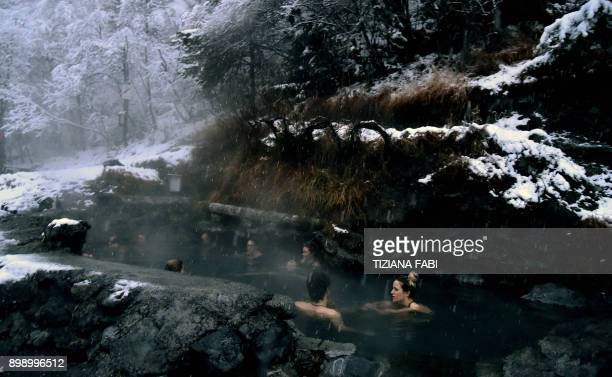 People take a bath in the natural hot water springs of Bormio on December 27 2017 / AFP PHOTO / TIZIANA FABI
