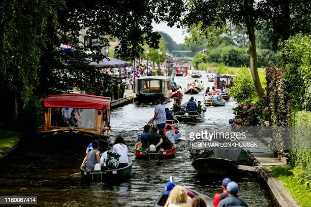 People take a boat ride on a river in Giethoorn, a well-known destination for tourists and day-trippers, on August 6, 2019. / Netherlands OUT