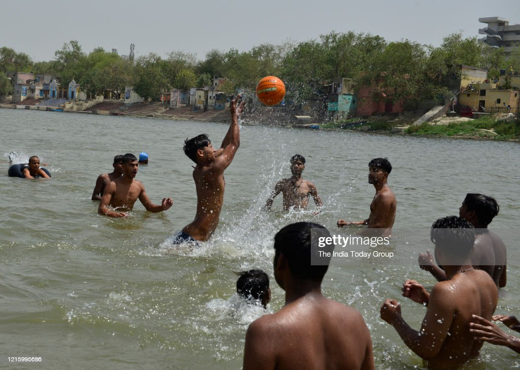 People take a dip in river Yamuna as the temperature has suddenly gone up... : News Photo