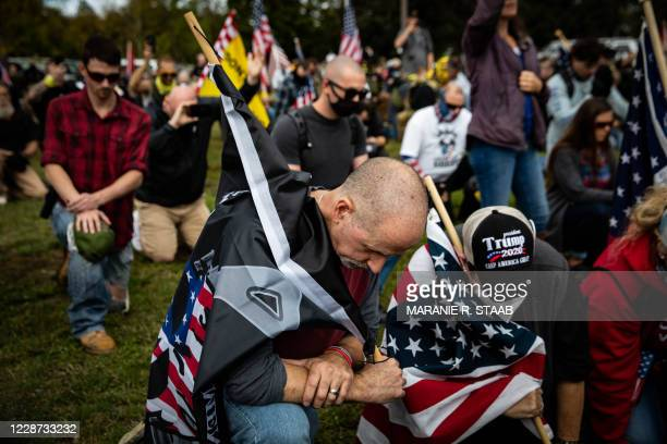 People take a knee as an organizer reads a prayer to the crowd of several hundred gathered during a Proud Boys rally at Delta Park in Portland,...