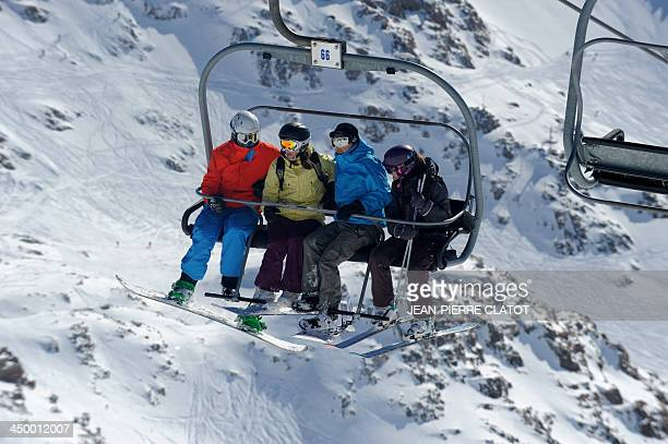 People take a lift to ski on the Sarenne glacier at the Alpe d'Huez resort in the French Alps on November 16 three weeks before the official opening...