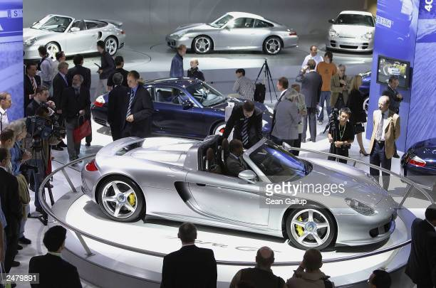 People take a look at the new Porsche Carrera GT sports car at the Frankfurt Auto Show September 10 2003 in Frankfurt Germany The show is open to the...