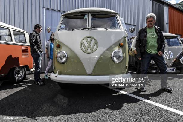 People take a look at Volkswagen vans on display in Le Versoud near Grenoble eastern France on May 20 2017 Lovers of the Volkswagen Kombi gathered on...