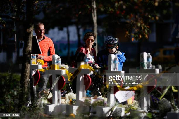 People take a look of the makeshift memorial for victims of Tuesday's terrorist attack along a bike path in lower Manhattan on November 3 2017 in New...