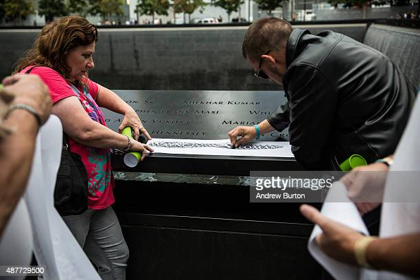 People take a moment to trace their loved one's names with charcoal and paper during an anniversary ceremony commemorating the terrorist attacks of...