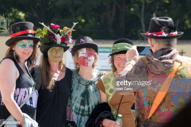 People take a photograph as the Glastonbury Dragons are paraded through the town as they take part in May Fayre and Dragon Procession in Glastonbury...