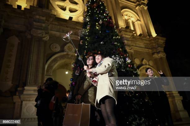 People take a photograph in front of a a Christmas tree outside a Catholic church in Beijing on December 24 2017 / AFP PHOTO / WANG ZHAO