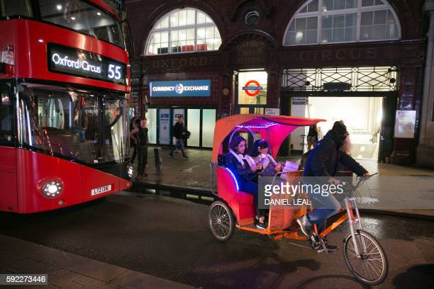 People take a ride in a taxibike outside Oxford Circus station in central London on August 19 2016 on the night of the launch of the 24hour night...