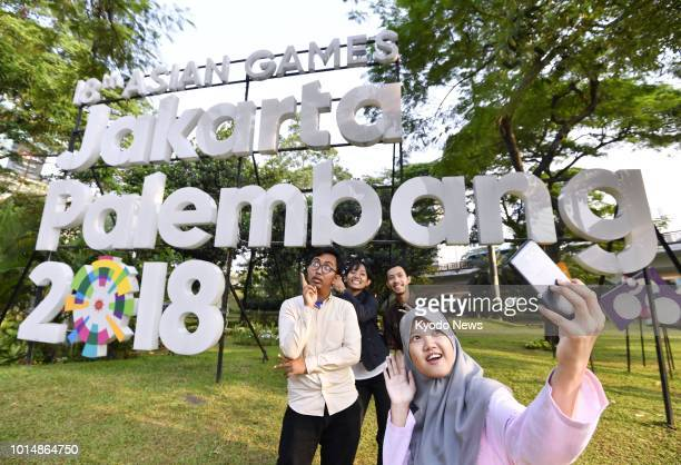 People take a selfie in front of an Asian Games 2018 promotional sign in Jakarta on Aug 8 2018 The event will be held from Aug 18 through Sep 2 in...