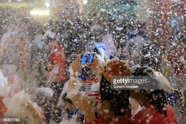 People take a selfie in the artificial snow made of foam at Tanglin Mall shopping centre on December 24 2014 in Singapore The mall has been holding...