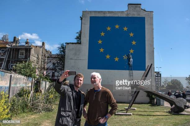 People take a selfie photograph in front of a recently painted mural by British graffiti artist Banksy depicting a workman chipping away at one of...
