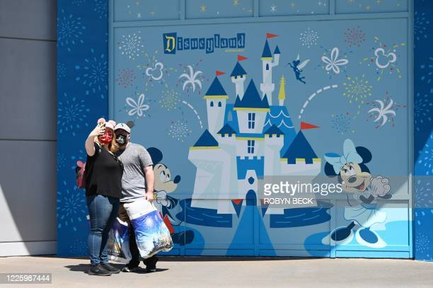 People take a selfie while visiting Downtown Disney in Anaheim, California on July 9 the first day the outdoor shopping and dining complex has been...