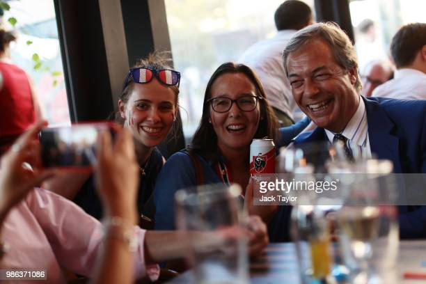 People take a selfie with Nigel Farage Member of the European Parliament and former Leader of the UK Independence Party as he watches England take on...