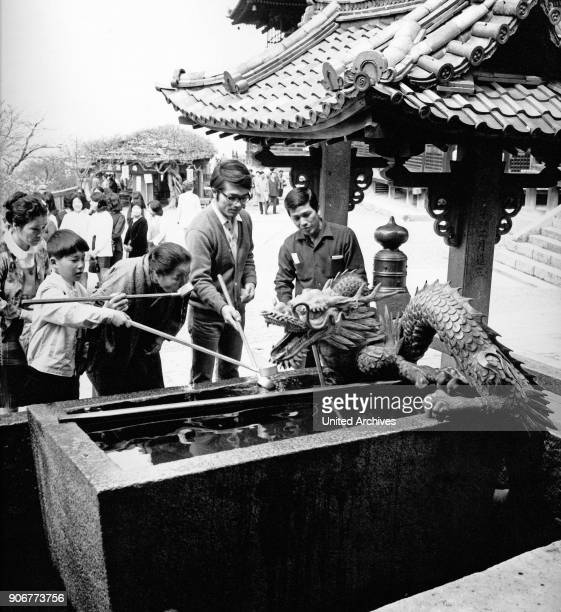 People take a sip of water from a holy well at a temple in Japan, 1960s.