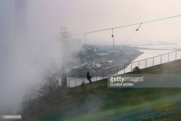 People take a ski lift up the artificial ski hill on the outdoor structure CopenHill in Copenhagen on December 6, 2020. - CopenHill is an urban...