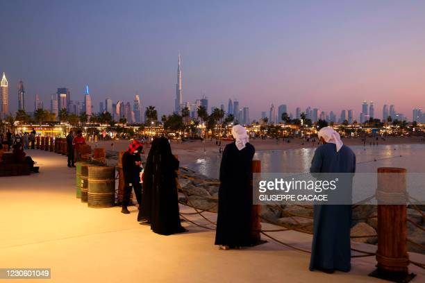People take a stroll by the seaside with a backdrop of the Dubai syline with Burj Khalifa, the world's tallest skyscraper, in the United Arab...