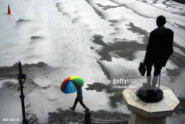 People take a stroll with umbrellas during hail storm on hail covered Ridgeon May 8 2018 in Shimla India Dust storms rain and thunder lashed out in...
