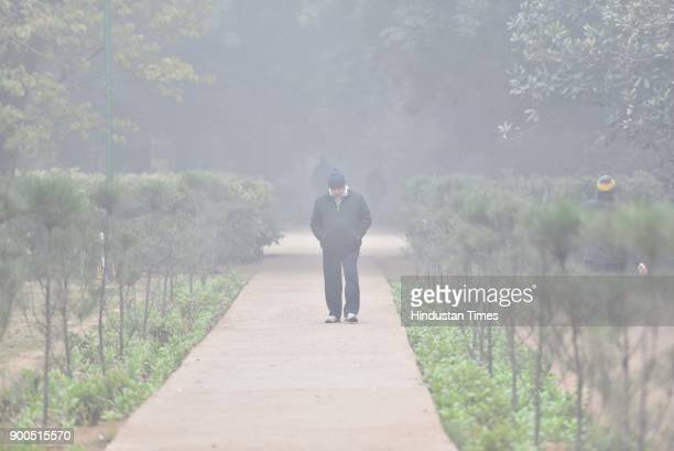 People take a walk in a park during winters amid heavy fog at Lodhi Garden on January 2 2018 in New Delhi India Cold wave conditions continued to...