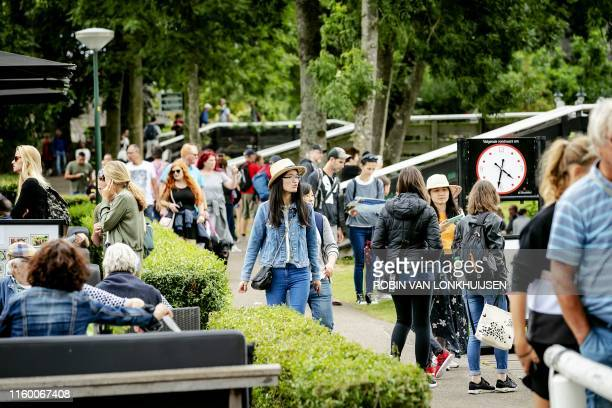 People take a walk in a street of Giethoorn, a well-known destination for tourists and day-trippers, on August 6, 2019. / Netherlands OUT