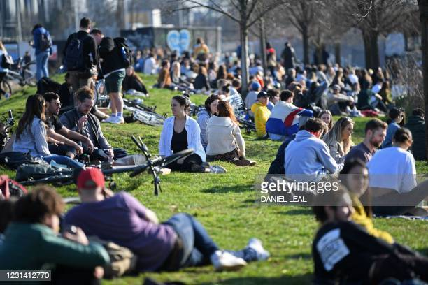 People take advantage of the good weather enjoying the winter sunshine in Hackney Wick, east London on February 27, 2021.