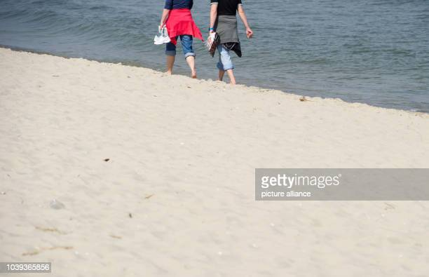 People take advantage of the sunny weather for a walk along the beach at the Baltic Sea in Zinnowitz,Germany, 22 April 2013. Photo: STEFANSAUER  ...