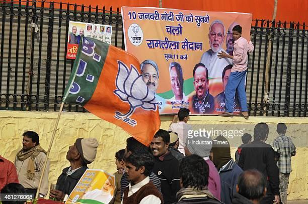People take away hoardings after the 'Abhinandan rally' of Prime Minister Narendra Modi at Ramlila Maidan on January 10 2015 in New Delhi India Modi...