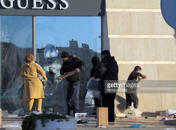 People take cloth from a looted store near a supermarket on January 15 2011 in La Gazella city near Tunis Tunisia's speaker of parliament took power...