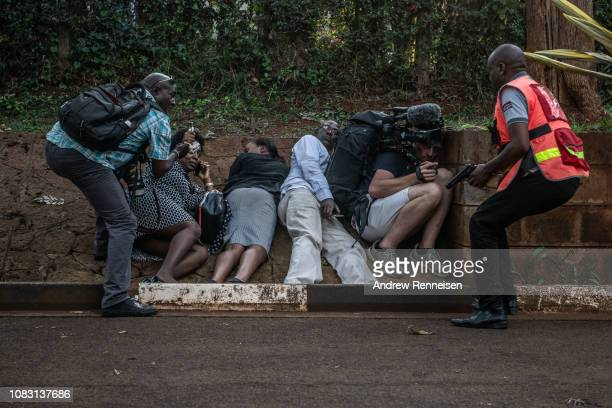 People take cover after hearing gunfire coming from the Dusit Hotel complex after being rescued on January 15 2018 in Nairobi Kenya A current...