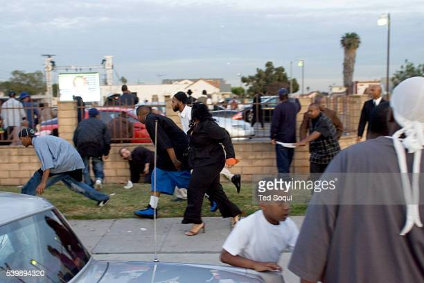 People take cover as gang members fire guns in the air at the funeral services for Stanley 'Tookie' Williams at Bethel AME Church in South Central...