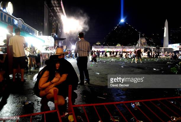 People take cover at the Route 91 Harvest country music festival after apparent gun fire was heard on October 1 2017 in Las Vegas Nevada There are...