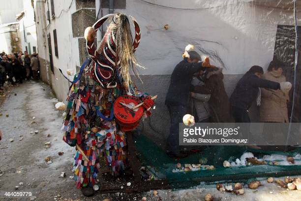 People take cover behind a net while others throw turnips at the Jarramplas as he makes his way through the streets beating his drum during the...