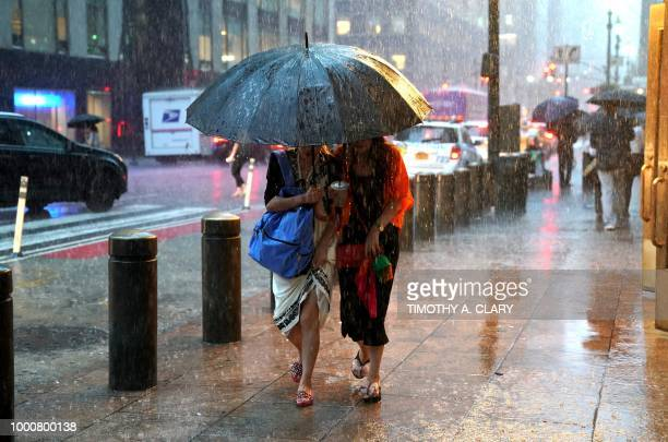 People take cover from the rain in Midtown New York on July 17 2018 as a sudden storm hit the area with flash food warning in the tristate area