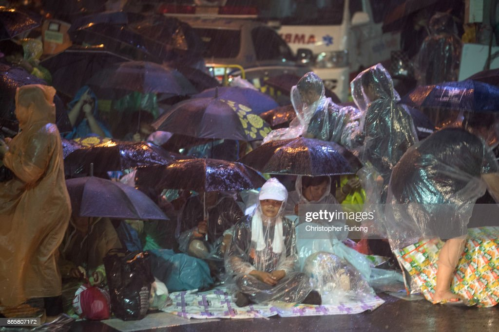 People take cover from torrential rain as they begin to queue and sleep on the streets overnight to attend Thailand's late King Bhumibol Adulyadej's cremation and funeral ceremony at the Royal Palace on October 24, 2017 in Bangkok, Thailand. The world's longest serving monarch King Bhumibol Adulyadej died on October 13, 2016. Rehearsals for the five day funeral of the much loved king are taking place around Bangkok's Grand Palace. The ceremonies will take place over five days culminating in the cremation of the king's body in a grand Royal Crematorium on October 26th.