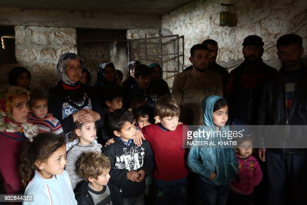 TOPSHOT People take cover in a cellar in the village of Qastal Koshk north of Afrin on March 16 amid battles between Turkishbacked forces and Kurdish...